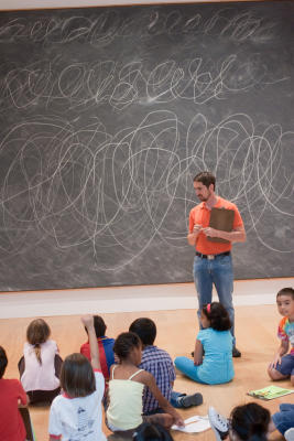 Instructor Kent Shaw invites campers to consider a Cy Twombly painting during a Writers In The Schools Summer Camp trip to the Menil Collection. The children used artworks on display as a startin